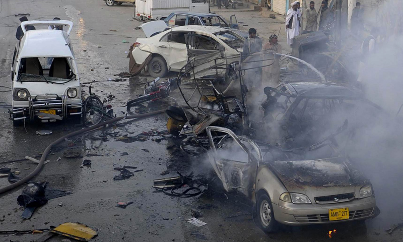Firefighters extinguish burning vehicles after a bomb explosion in Quetta on Oct 30, 2013. — AFP Photo