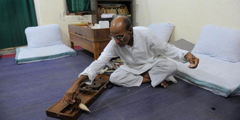 Ashram co-ordinator Rameshbhai Trivedi prepares cotton thread on a manual 'charkha' or a weaving tool inside his office at Kochrab Ashram. — Photo by AFP