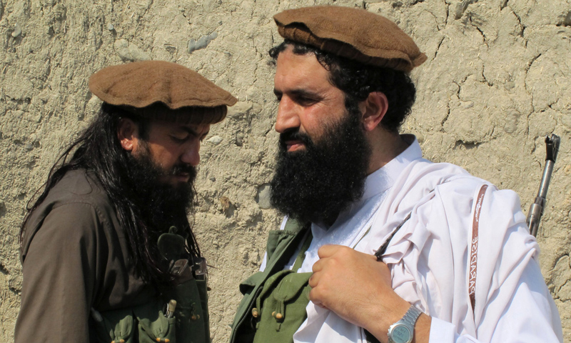 In this Oct 5, 2013 photo, Pakistani Taliban spokesman Shahidullah Shahid, right, arrives for an interview at an undisclosed location in Pakistan's tribal areas.—AP Photo