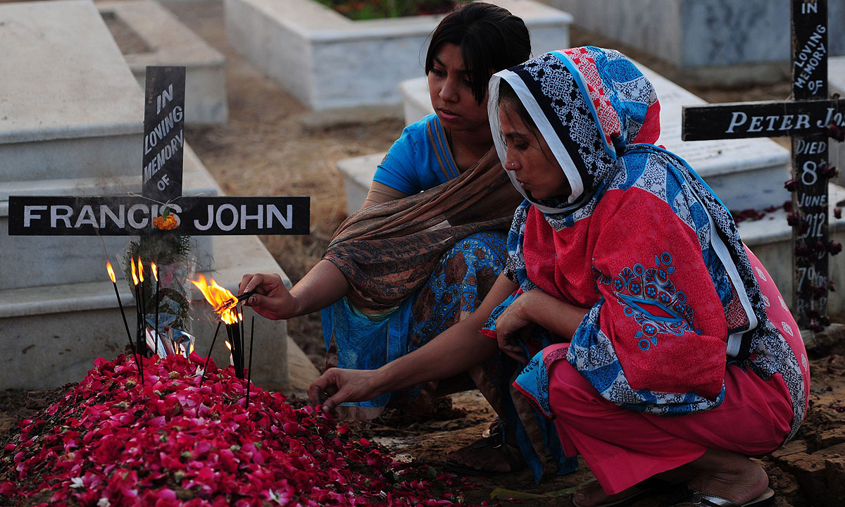Pakistani Christians visit the grave of a relative at the Catholic cemetery during All Souls Day in Karachi on November 2,  2013.