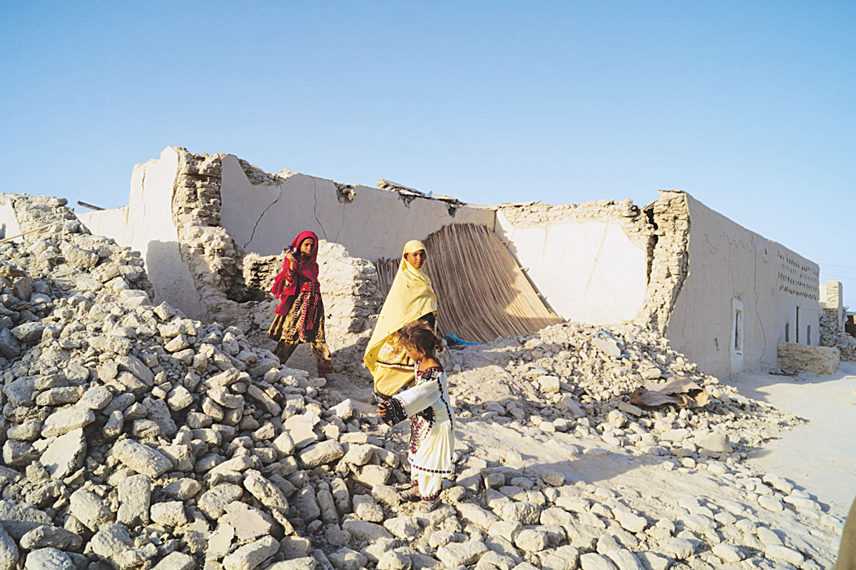 A little girl rummaging through the rubble of a collapsed mud house. -Photos by ISPR and White Star