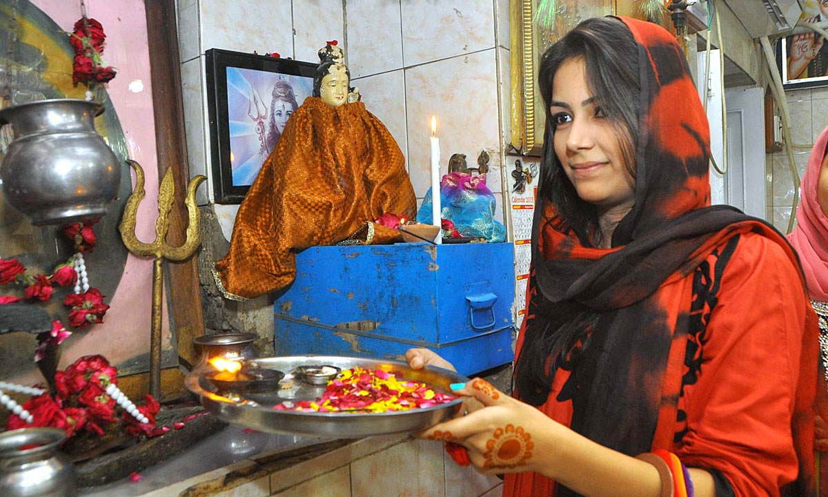 A member of Larkana's Hindu community performs a religious ritual to celebrate Dewali, at a local temple. – Photo by APP