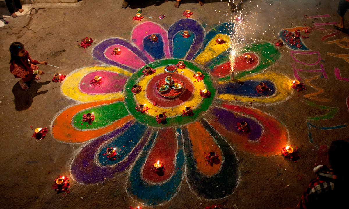 """A young Pakistani Hindu sits near a """"rangoli,"""" which are traditional patterns made from coloured powders, during Diwali celebrations at the Shree Swami Narayan Temple in Karachi. – Photo by Reuters"""