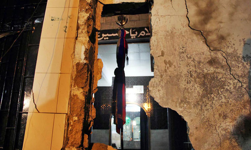 Alam (war flag) can be seen through a broken wall of an Imambargah after twin bomb blasts near Pahar Ganj area in in Karachi's North Nazimabad on Wednesday. – Photo by Online