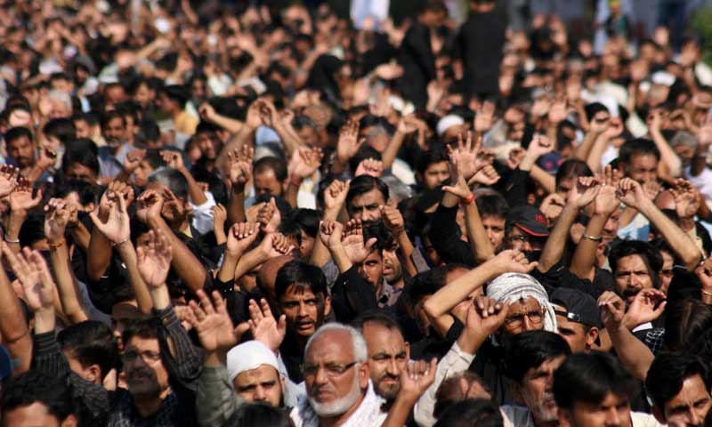 Mourners raise their hands during a Muharram mourning procession. — Photo by INP