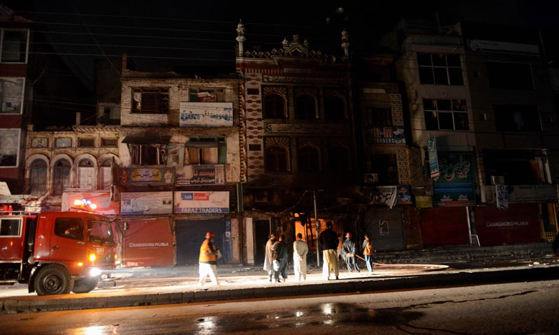 Rescuers extinguish fires in Rawalpindi on Nov 15, 2013. — Photo by AFP