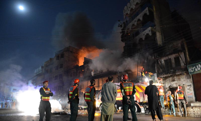 Rescuers and security personnel gather in front of a burning market in Rawalpindi on Nov 15, 2013. — Photo by AFP