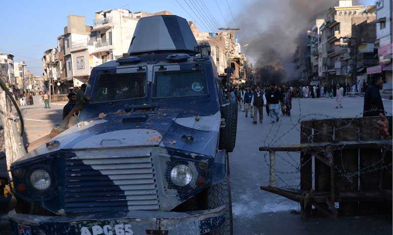 A police armoured vehicle leaves the site following a clash in Rawalpindi on Nov 15, 2013. — Photo by AFP