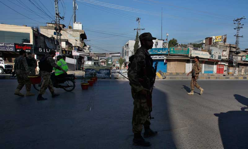 Army soldiers stand guard as others block a road during a curfew in Rawalpindi, Nov 16, 2013. — AP