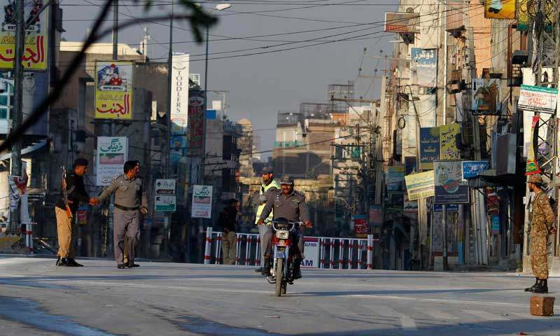 An army soldier and police officers stand guard during a curfew in Rawalpindi, Nov 16, 2013. — AP