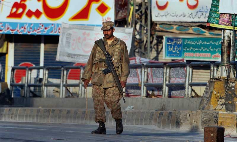 An army soldier patrols on a street during a curfew in Rawalpindi, Nov 16, 2013. — AP