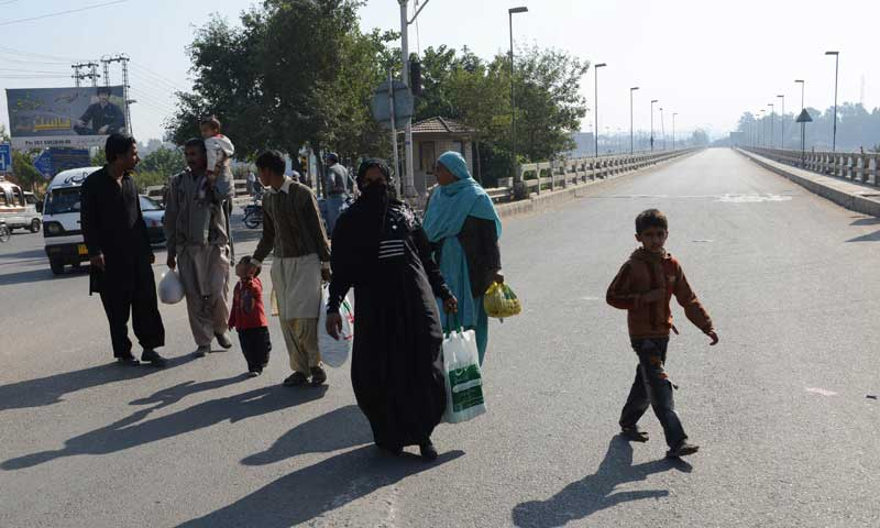 People search for available transport during a curfew in Rawalpindi on Nov 17, 2013. — AFP