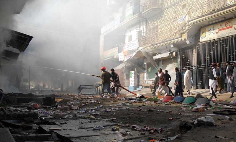 Firefighters extinguish a fire at a market after a clash in the northwestern city of Kohat, Nov 18, 2013. — Photo by AFP