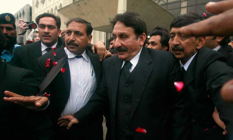Supreme Court Chief Justice Iftikhar Chaudhry (C) is escorted to his office in Islamabad in this March 24, 2009 file photo. — Reuters