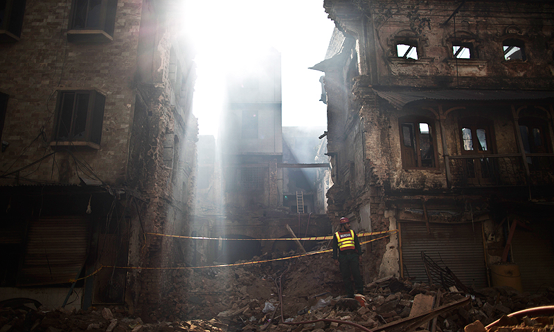 A rescue worker stands in the rubble of a building, which was burnt and destroyed in Friday's sectarian clashes, in Rawalpindi. -Photo by AP