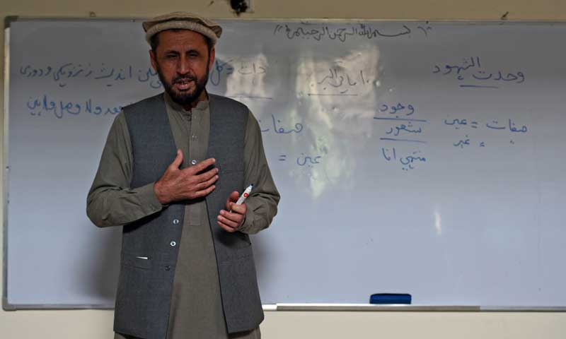 In this picture taken on Nov 2, 2013, Afghan university professor of Pashto literature Fazal Wali Nagar talks to his students at a classroom in Jalalabad. — AFP