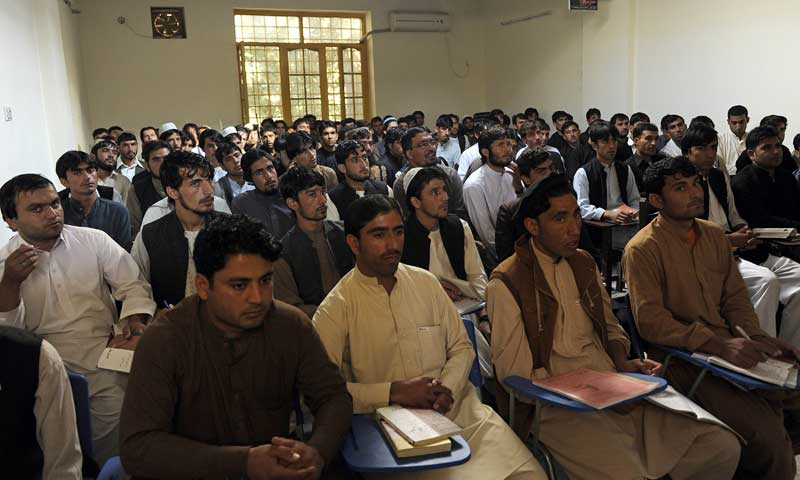 In this picture taken on Nov 2, 2013, Afghan University Pashto literature students listen to Fazal Wali Nagar at a classroom in Jalalabad. — AFP