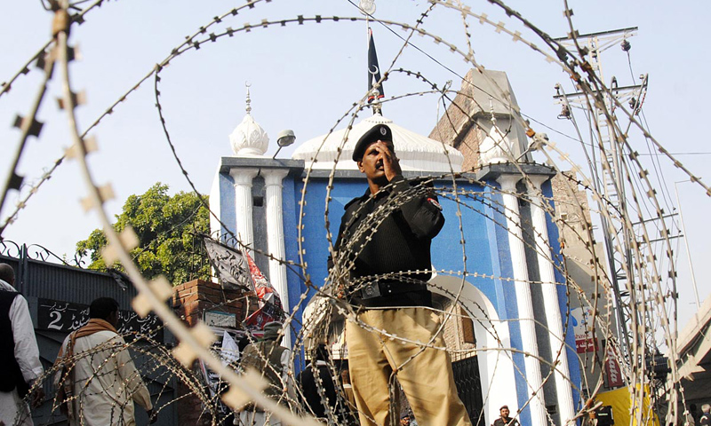 Policemen stand guard outside Karbala Gamay Shah imambargah in Lahore.—Online Photo