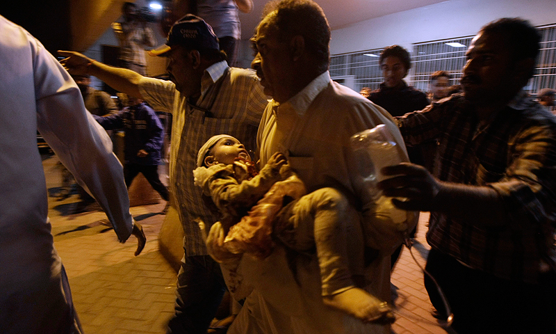 A Pakistani man rushes to a hospital carrying a child injured in a bomb blast, in Karachi early Saturday. -Photo by AP