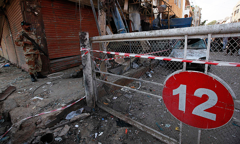 A Rangers personnel guards the site of the bomb blast in Karachi. -Photo by Reuters