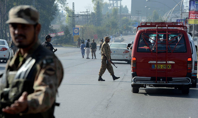 Pakistan soldiers keep watch outside at a checkpoint during a curfew in Rawalpindi on Nov 16, 2013. — AFP Photo
