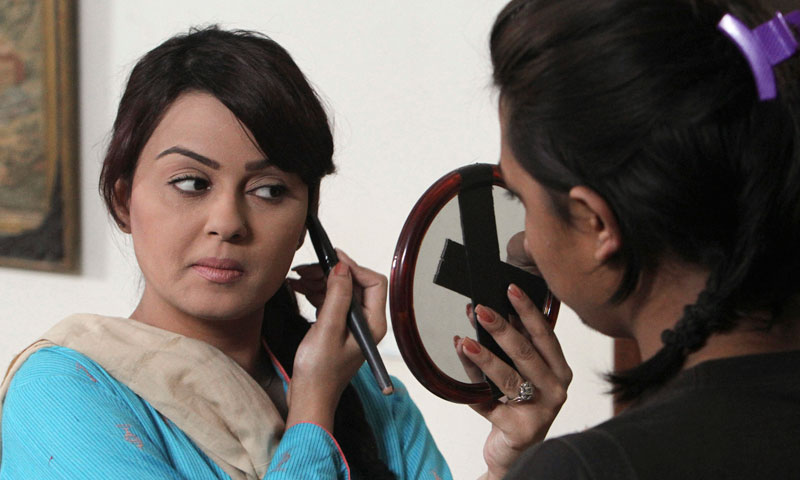 "Pakistani TV star Javeria Abbasi applies makeup on her face before acting a scene in the drama serial ""Mere Apne"" or ""My Loved Ones,"" at a studio in Karachi, Pakistan. — Photo by AP"