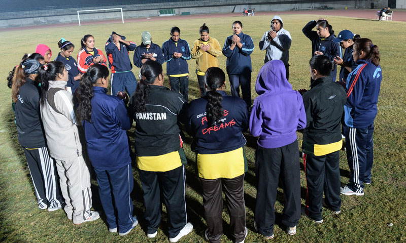 Members of the Pakistan women's Kabaddi team pray before a practice match at the Punjab Stadium in Lahore. —Photo by AFP