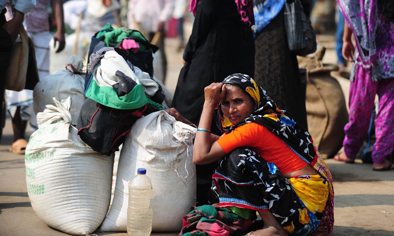 A Bangladeshi commuter waits at a bus terminal during a blockade organised by Bangladesh Nationalist Party activists and their supporters in Dhaka on November 30, 2013. — Photo by AFP