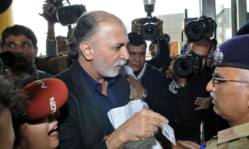 Indian magazine editor Tarun Tejpal (C) shows his identity card to an official as he enters the airport in New Delhi on November 29, 2013, ahead of travelling to the western city of Goa where he is due to be questioned by police. Tehelka's founder and editor Tarun Tejpal is under investigation over claims he sexually assaulted a woman twice in a hotel in the holiday state of Goa.   — Photo by AFP