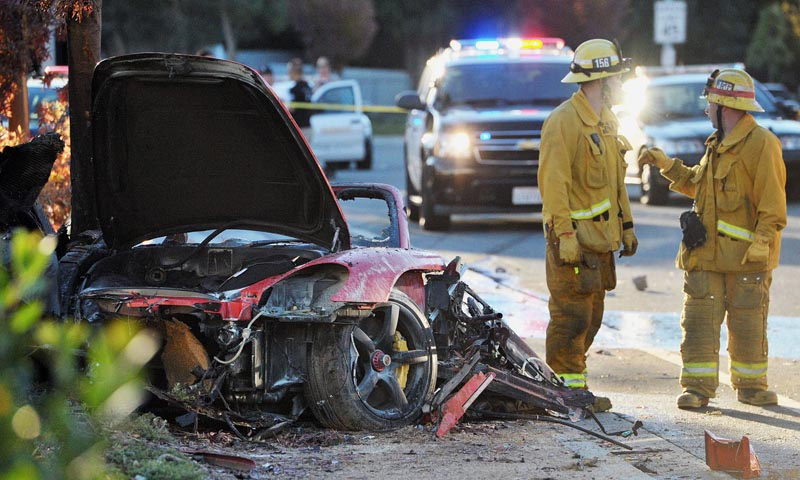 Sheriff's deputies work near the wreckage of a Porsche that crashed into a light pole on Hercules Street near Kelly Johnson Parkway in Valencia, Calif., on Saturday, Nov. 30, 2013. — Photo by AP