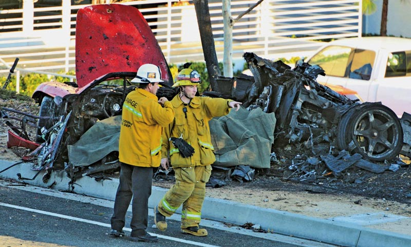 Sheriff's deputies work near the wreckage of a Porsche that crashed into a light pole on Hercules Street near Kelly Johnson Parkway in Valencia, Calif., on Saturday, Nov. 30, 2013.— Photo by AP