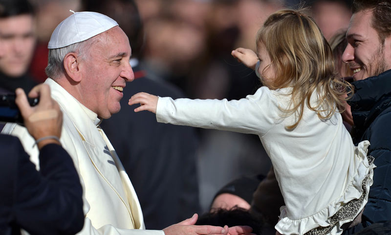 Pope Francis is about to hug a young girl during his general audience in St Peter's square at the Vatican. -AFP Photo