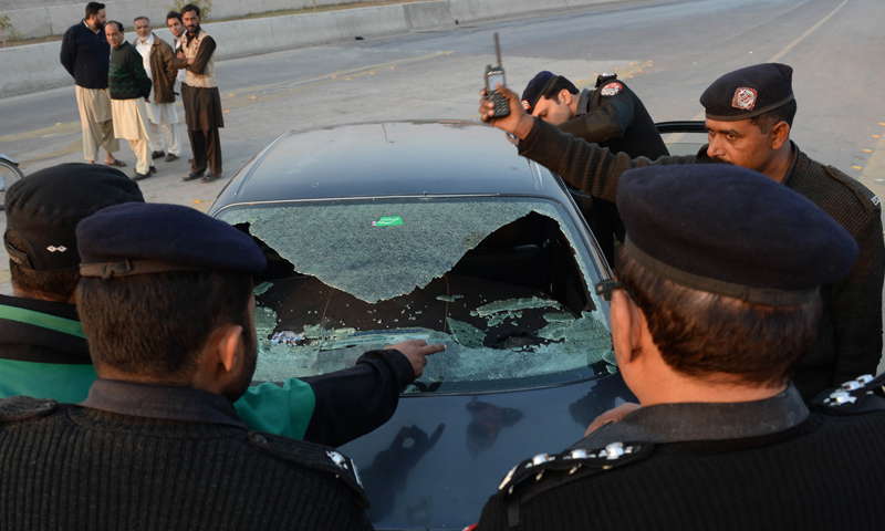 Police officials examine the bullet-riddled vehicle of ASWJ leader Maulana Shamsur Rehman Muavia after an attack by gunmen in Lahore on December 6, 2013.—AFP Photo