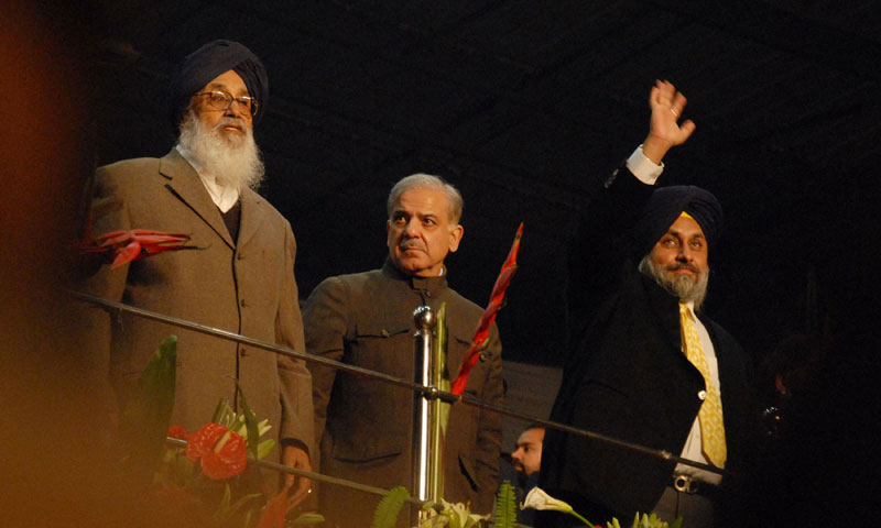 Punjab Chief Minister Shahbaz Sharif (C), Indian Punjab Chief Minister Prakash Singh Badal (L) and deputy Chief Minister Sukhbir Singh Badal greet the crowd during the final match of fourth World Cup Kabaddi Punjab 2013 tournament in Ludhiana. — Photo by AFP