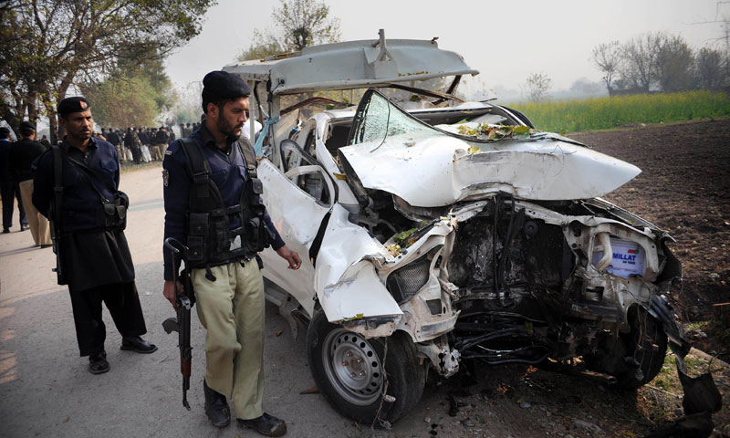 Police officials examine the wreckage of a bomb disposal vehicle after a roadside bomb explosion on the outskirts of Peshawar on December 16, 2013.  — Photo by AFP