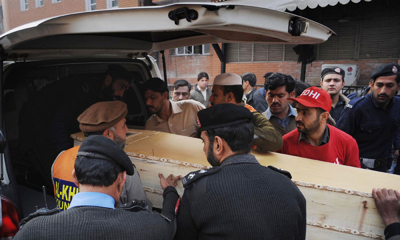 Policemen place the coffin of bomb disposal officer Abdul Haq into an ambulance following a roadside bomb explosion in Peshawar on December 16, 2013.  — Photo by AFP