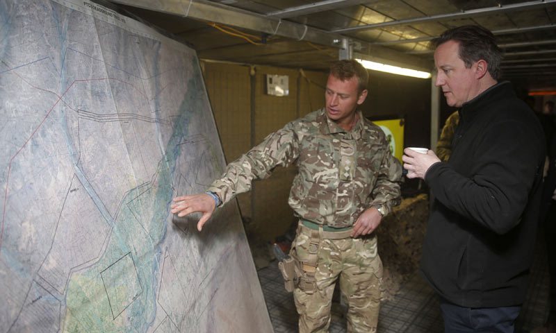 Britain's Prime Minister David Cameron (R) listens to a briefing by a British army officer at the forward operating base Sterga II, in Helmand province, southern Afghanistan. -Reuters Photo