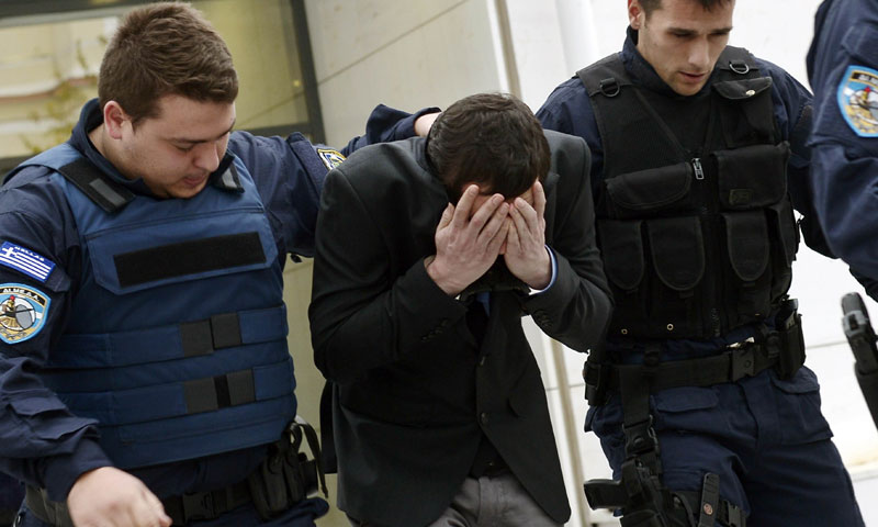 Police officers escort one of the two suspected members of the Greek neo-Nazi party Golden Dawn accused of stabbing a 27-year-old Pakistani man to death in Athens on December 18, 2013. – AFP