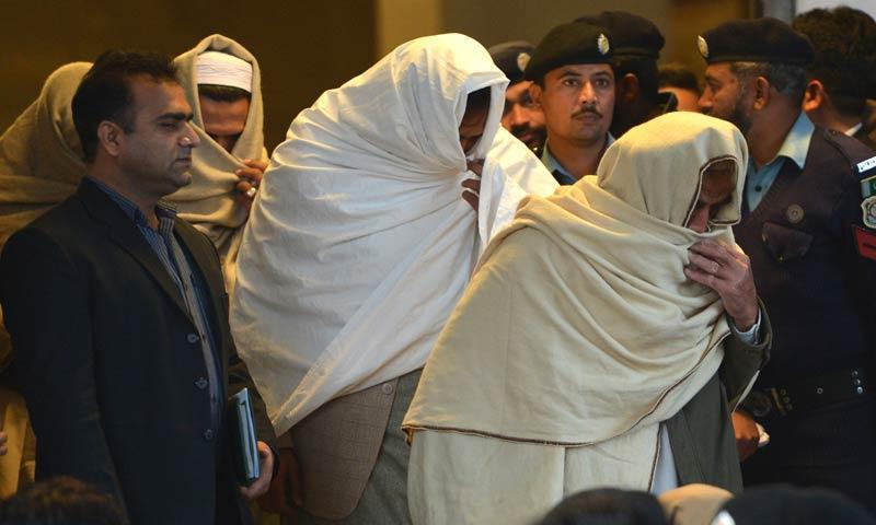 Policemen escort newly-identified missing persons following an identification process as they leave the Supreme Court building in Islamabad. – AFP Photo/File