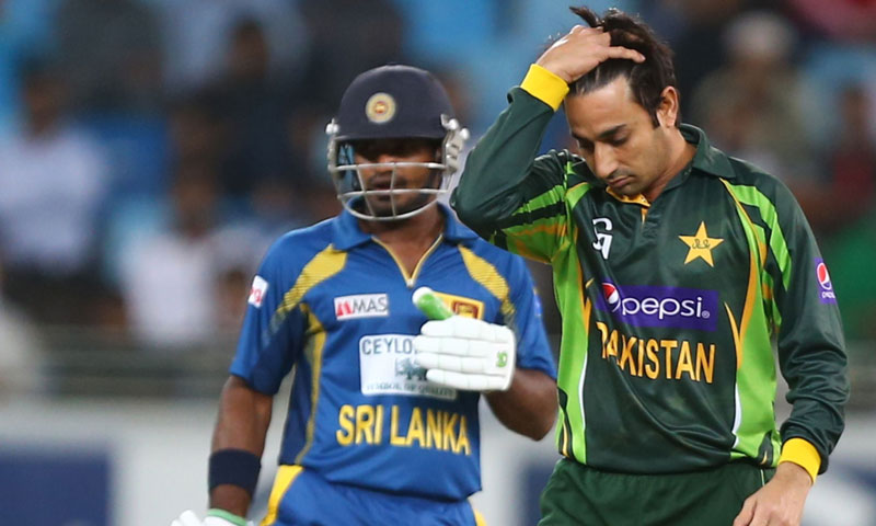Bowler Saeed Ajmal (R) of Pakistan gestures after delivering the ball to batsman TM Dilshan (unseen) of Sri Lanka during their 2nd One Day International cricket match in Dubai, on December 20, 2013.  – AFP