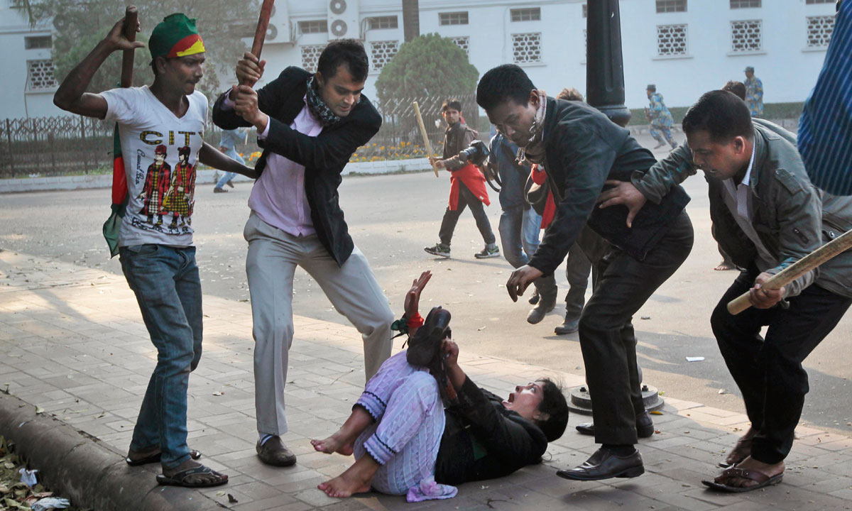Supporters of the ruling Bangladesh Awami League beat a lawyer and supporter of the main opposition Bangladesh Nationalist Party (BNP) during a protest by opposition activists in Dhaka, Bangladesh, Sunday, December 29. – Photo by AP