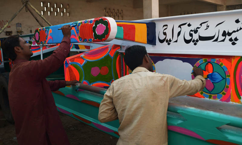 In this photograph taken on November 22, 2013, Pakistani truck painters add the finishing touch to the bodywork of a truck in Karachi. Pakistan's truck artists, who transform ugly lorries into flamboyant moving works of art, fear boom times for their trade could be at an end as Nato winds down its mission in Afghanistan.   — Photo by AFP