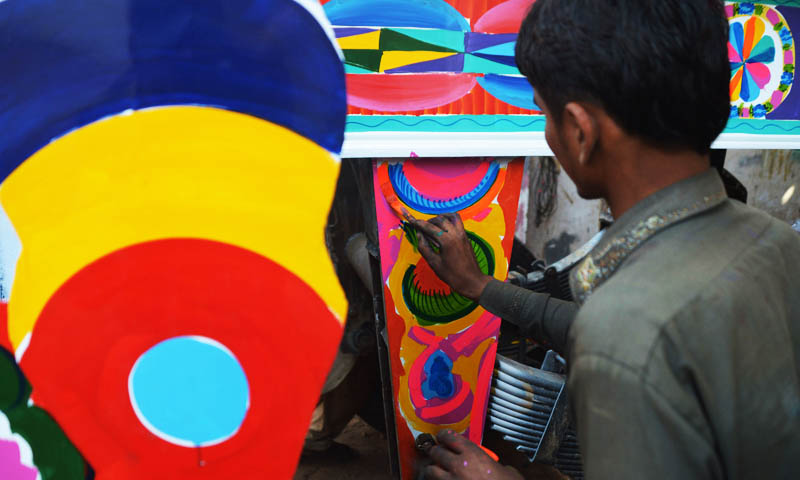 In this photograph taken on November 22, 2013, a Pakistani truck painter adds the finishing touches to the bodywork of a truck in Karachi. Pakistan's truck artists, who transform ugly lorries into flamboyant moving works of art, fear boom times for their trade could be at an end as Nato winds down its mission in Afghanistan.   — Photo by AFP