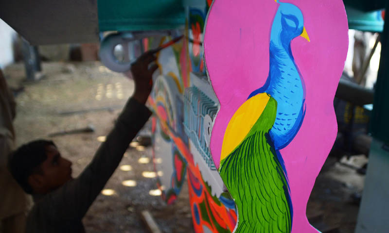 In this picture taken on November 22, 2013, a Pakistani truck painter adds the finishing touches to the bodywork of a truck in Karachi. Pakistan's truck artists, who transform ugly lorries into flamboyant moving works of art, fear boom times for their trade could be at an end as Nato winds down its mission in Afghanistan.   —  Photo by AFP