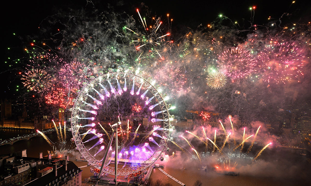 Fireworks explode over the London Eye and the Houses of Parliament along the river Thames during the New Year celebrations in central London just after midnight on January 1, 2014. – Photo by AFP
