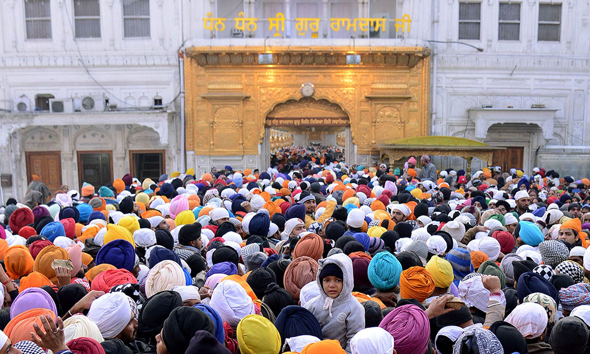 Indian Sikh devotees wait for their turn to pay homage at the Sikh Shrine, The Golden Temple in Amritsar on January 1, 2014. Thousands of Sikh devotees from across India and abroad are preparing to pay obeisance on the occasion of New Year at the temple in northern India. – Photo by AFP