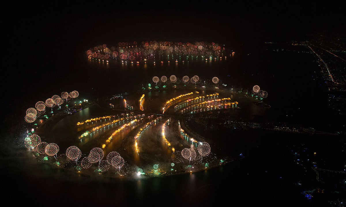 """In this photo provided by Dubai World Record 2014, fireworks explode over Palm Jumeirah Island, front, and World Islands, rear, to celebrate the New Year on Wednesday, Jan. 1, 2014 as the city attempts to breaks the Guinness World Record for the """"Largest Firework Display."""" – Photo by AP"""