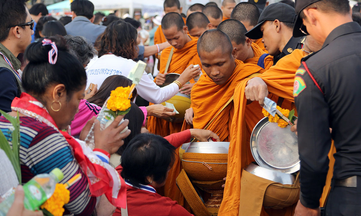 Buddhist monks take morning alms during a New Year offering held by anti-government protesters at the Democracy Monument in Bangkok, Thailand Wednesday, Jan. 1, 2014. – Photo by AP