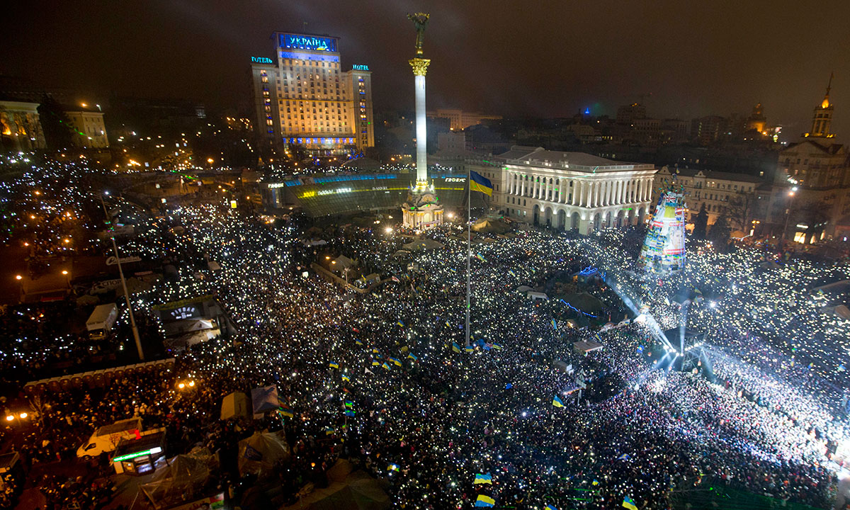 Pro-European Union activists hold lights while singing the Ukrainian national anthem as they celebrate the New Year in Kiev's main square early Wednesday, Jan. 1, 2014, in Ukraine. At least 100,000 Ukrainians sang the country's national anthem together at the square on New Year's Eve in a sign of support for integration with Europe. Opposition leaders had called on Ukrainians to come to the Maidan on New Year's Eve and sing the national anthem in an act of defiance and what they expected could be the record-breakin