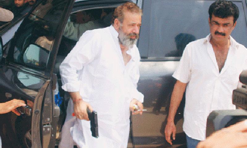 چوہدری اسلم روایتی سفید لباس اور اپنی مخصوص گن کے ساتھ اپنی گاڑی سے باہر آرہے ہیں۔ فائل تصویر